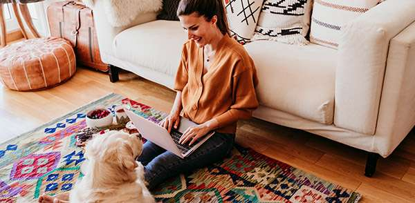 Woman sat on the floor with dog and laptop
