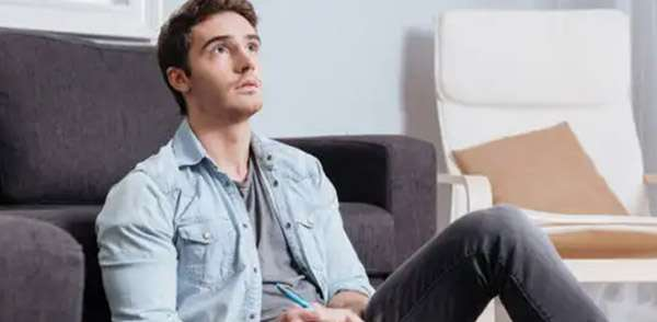 Man looking up sat by a sofa