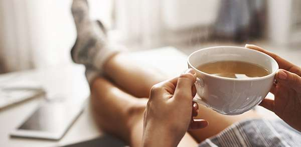 Person holding warm cup of tea